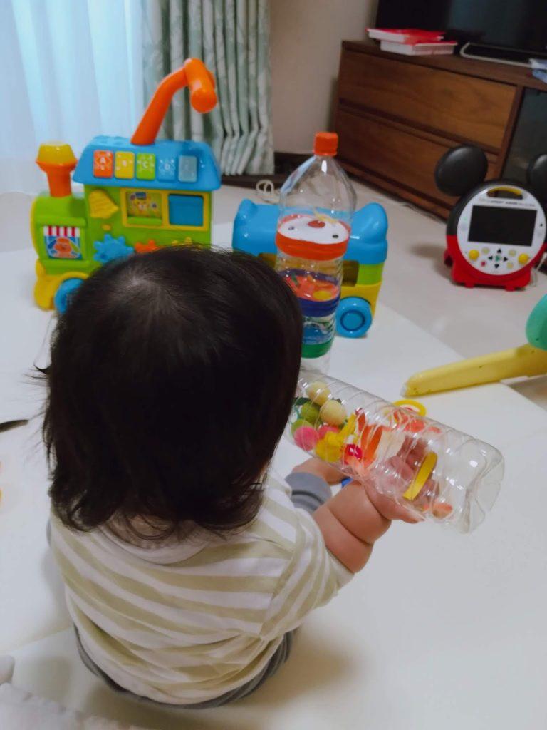 ペットボトルの手作りおもちゃを真剣に見つめる子供