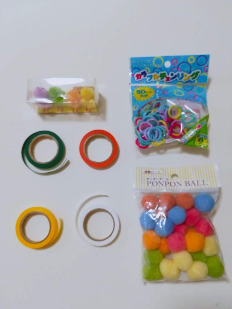 ペットボトルの手作りおもちゃの材料となるひよこ、紙テープ、カラフルリング、ぽんぽん