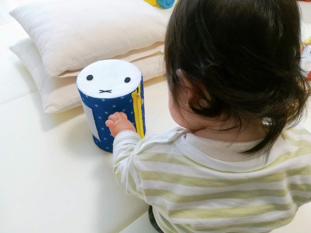 ミルクの空き缶で手作りしたミッフィーの太鼓の手触りを楽しむ子供