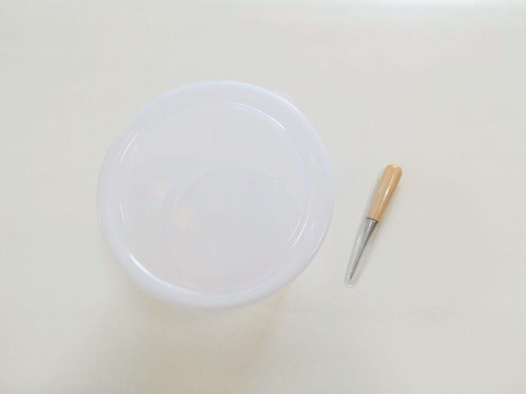 透明のプラスチック容器のふたに、目打ちで穴をあけた図