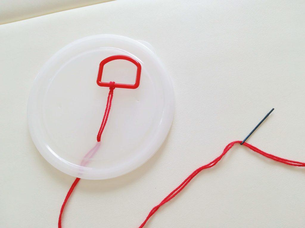 紐をとおしたDカンを、透明プラスチック容器のフタにとおした図
