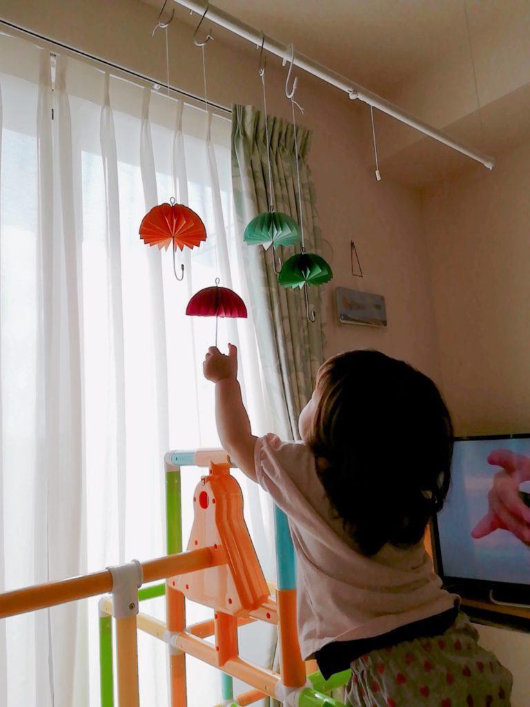 完成した傘モビールで遊ぶ子供