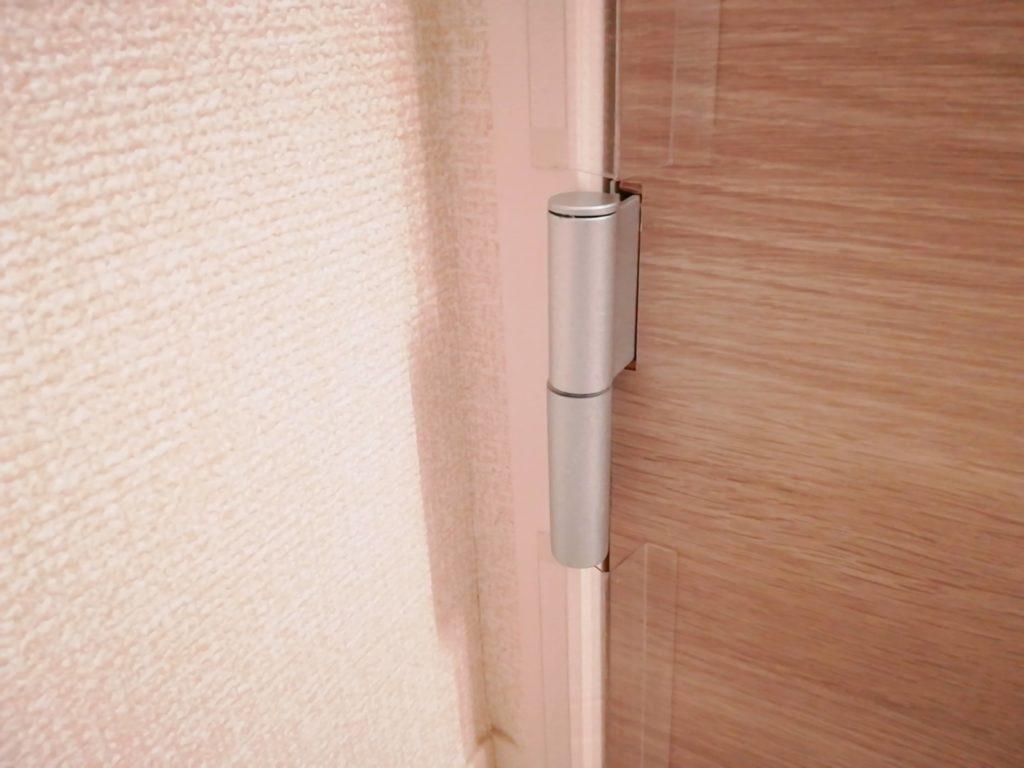 指はさみ防止グッズ「はさマンモス」を取り付けたドアのヒンジ部分拡大図