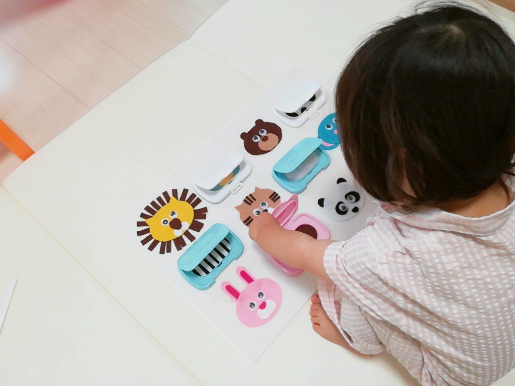 動物いっぱいのセンサリーボードで遊ぶ娘